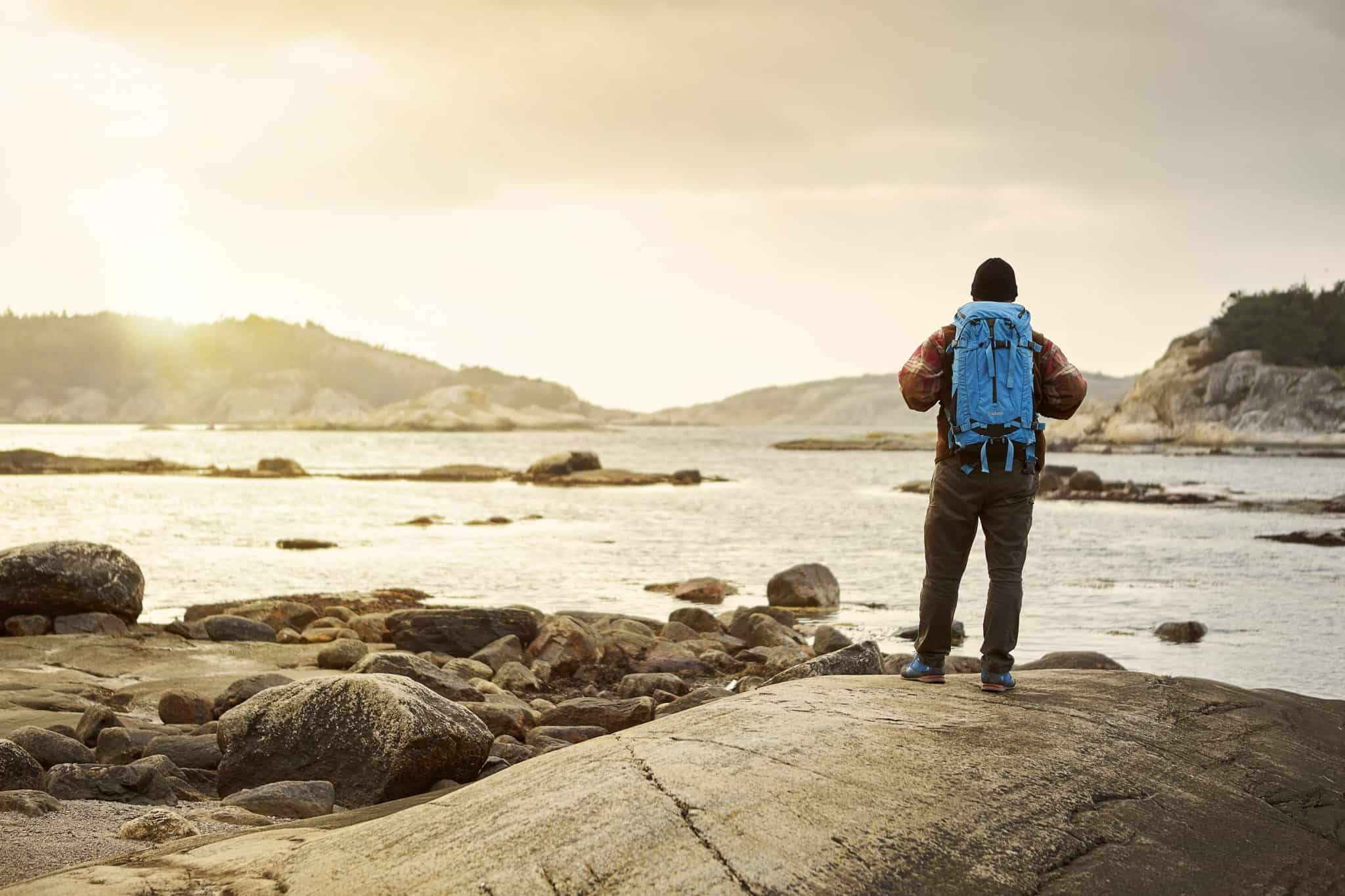 Person med ryggsäck blickar ut över Bohusläns oerhört vackra skärgård på västkusten.