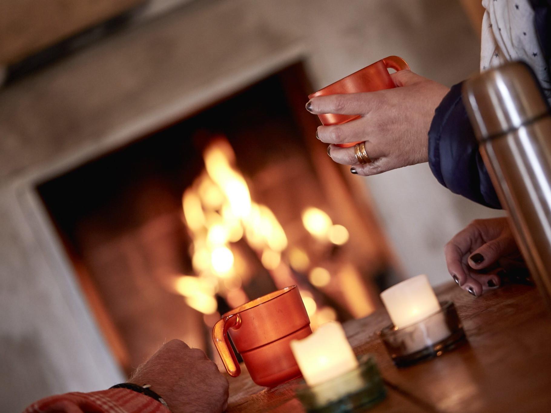 Person dricker kaffe vid öppen eld.