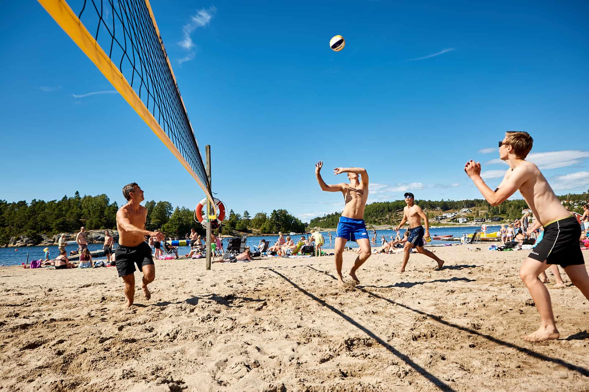 fyra personer spelar volleyboll.