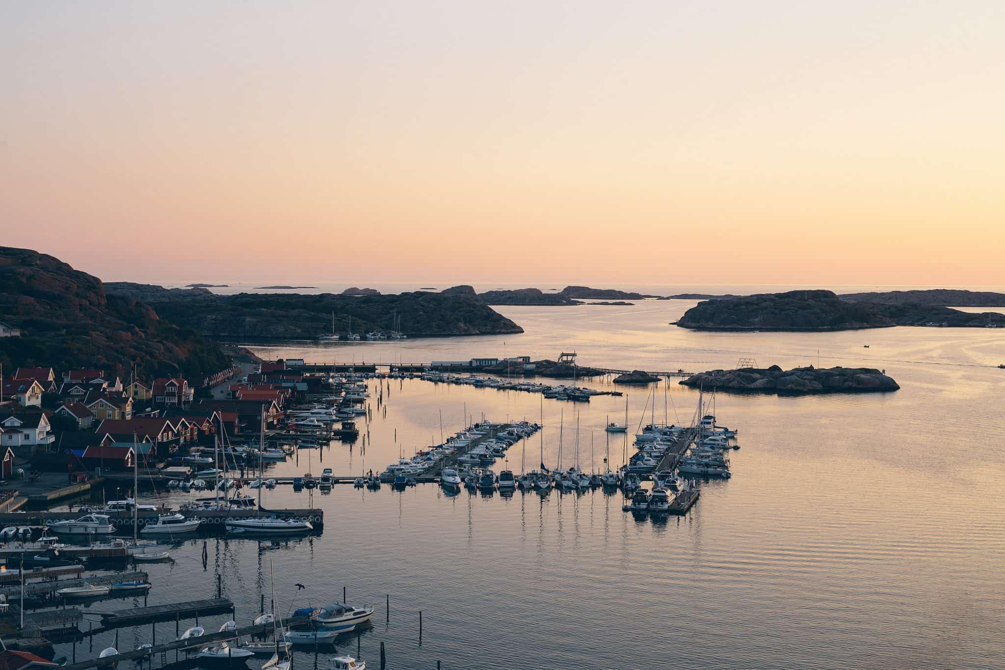 Solnedgång över det idylliska Bohuslän med dess klippor, båtar och semesterfirare.