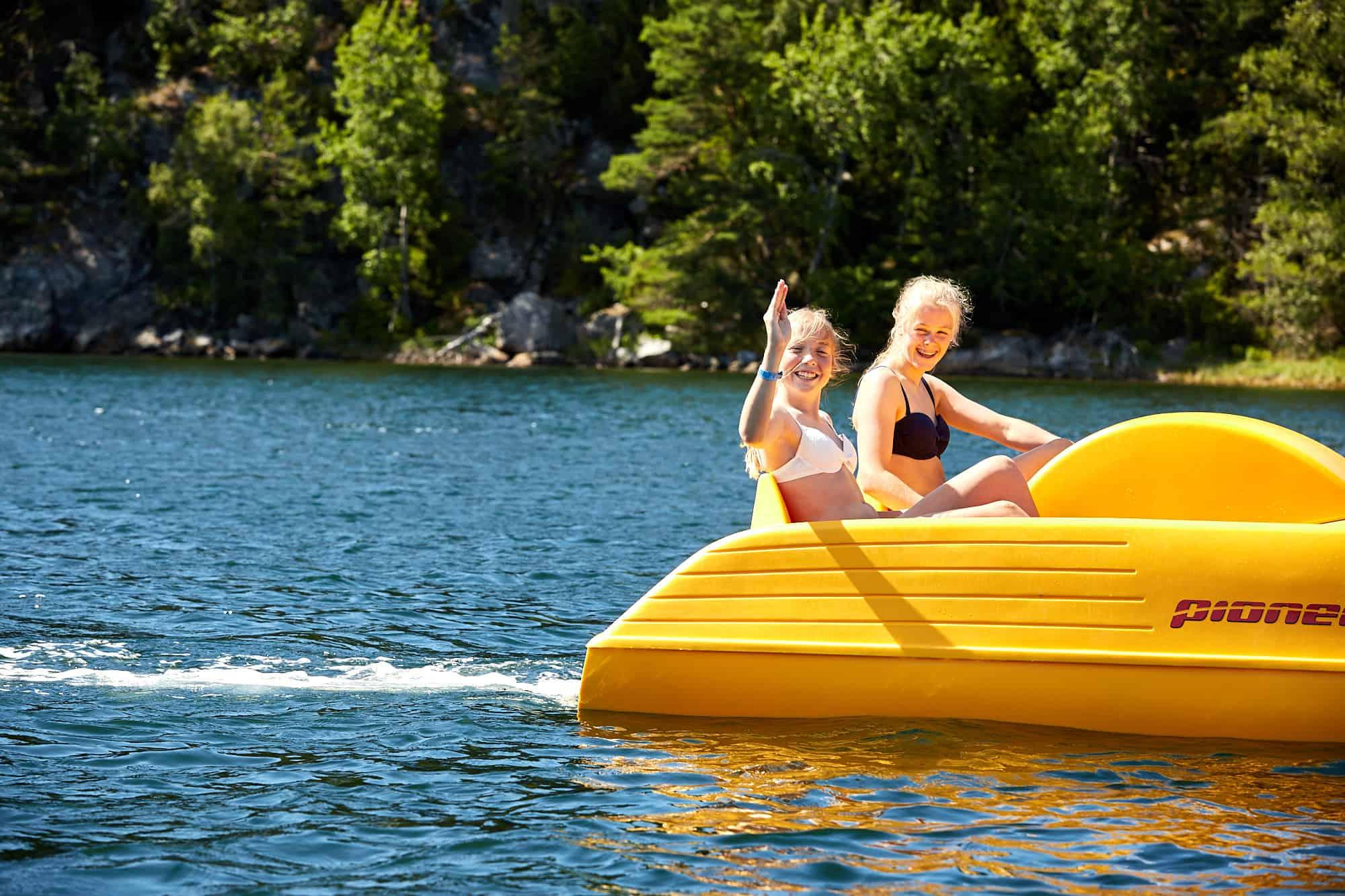 Två tjejer i en trampbåt en solig dag på västkusten, på Lagunen utanför Strömstad.
